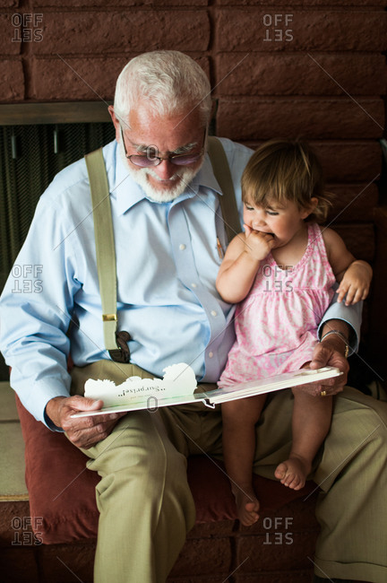 A grandfather reads to his granddaughter