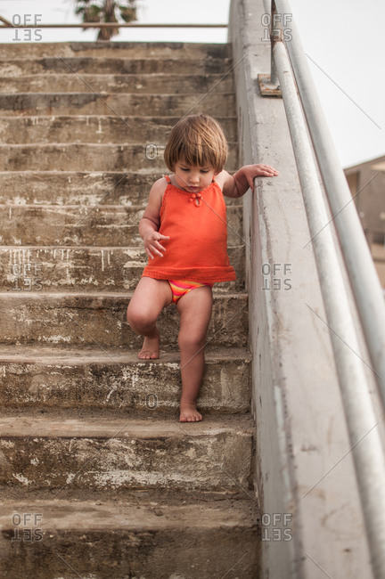 A little girl walks down stairs