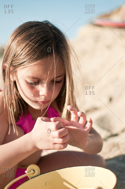 A girl examines sand at the beach