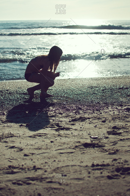 A girl crouches by the water