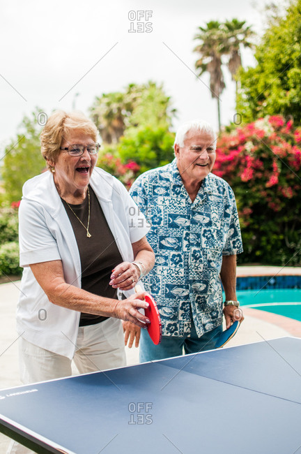 An elderly couple plays table tennis