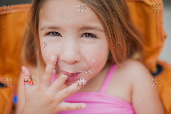 A girl licks icing off her finger