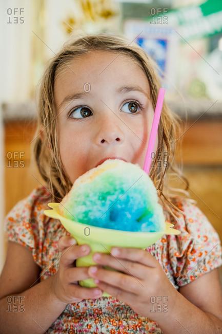 A girl eats a large italian ice