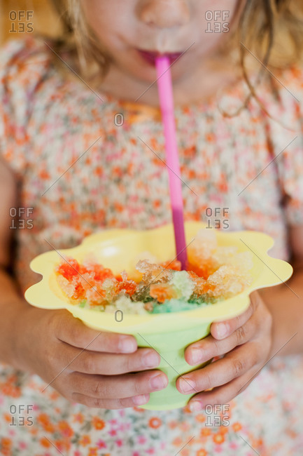 A girl drinks melted italian ice through a straw
