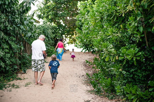 Grandparents walk with their grandchildren to the beach