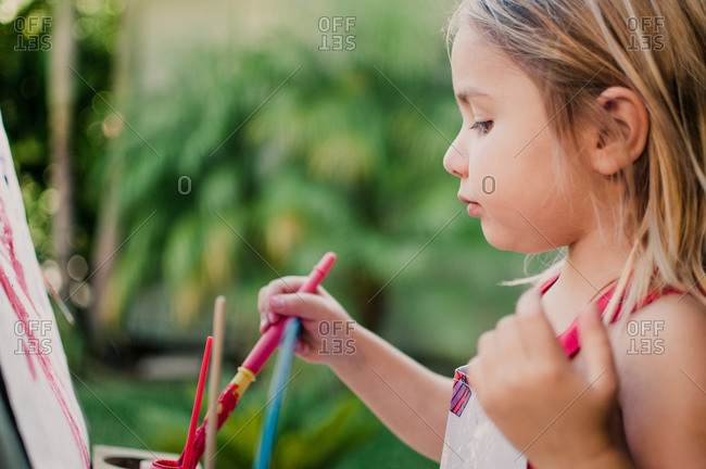 A girl paints on an easel