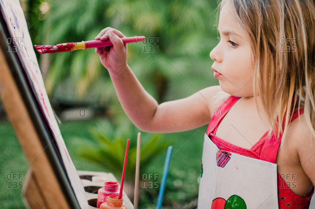 A girl painting on an easel