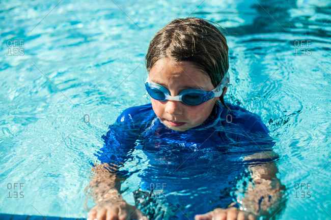 A boy hanging onto the edge of a pool