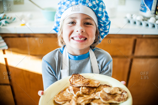 A little boy holds up a plate of pancakes