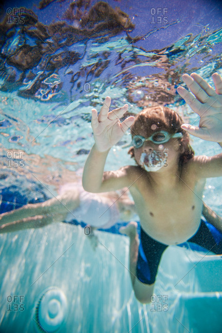 A boy and girl swim underwater