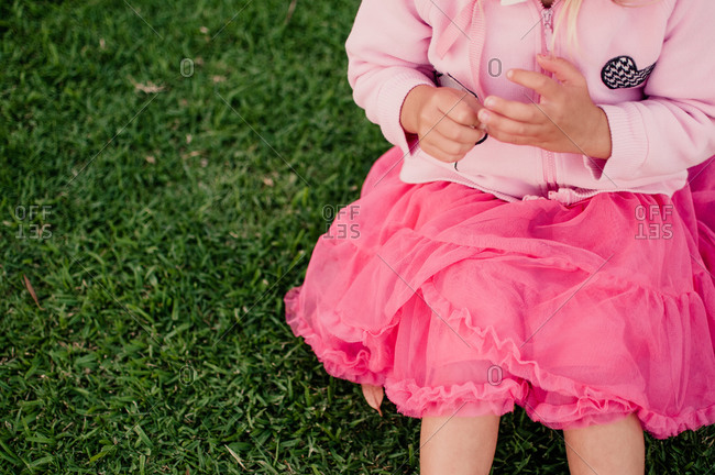 A little girl sitting on the grass