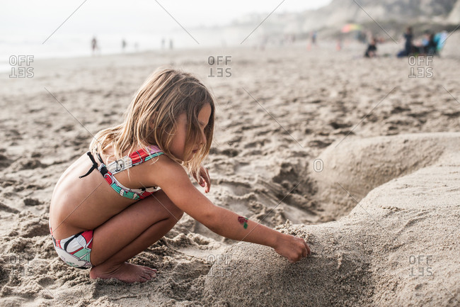 A little girl makes a sand sculpture
