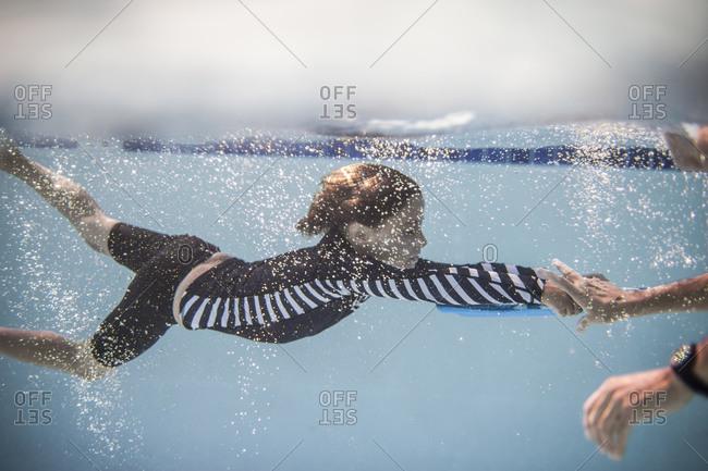 A boy swims in a pool