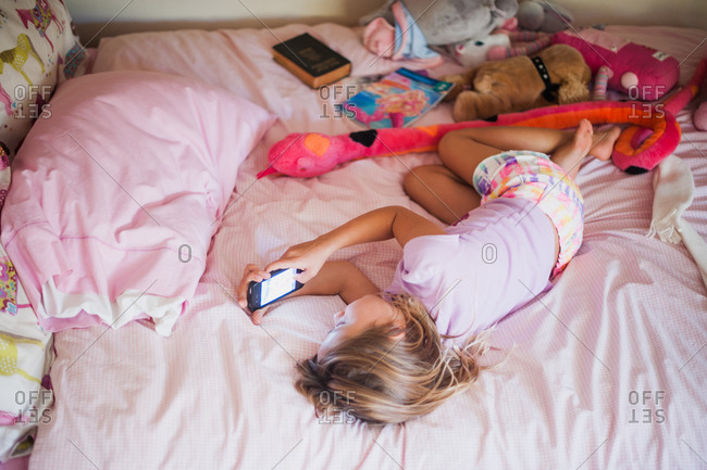 A girl lying on her bed with a smartphone