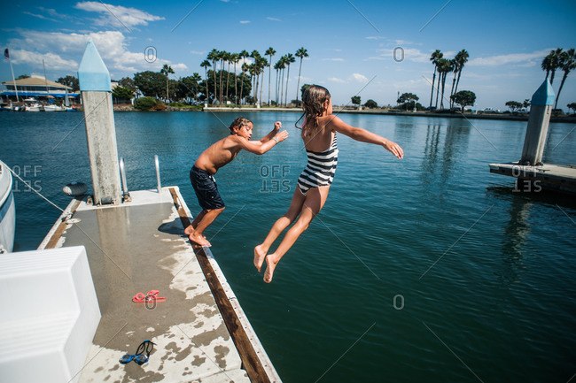 A boy and girl jump off a dock