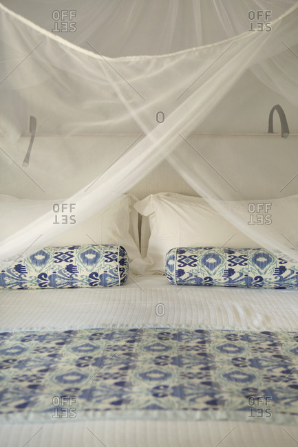 Bed in a hotel with blue patterned pillows and canopy