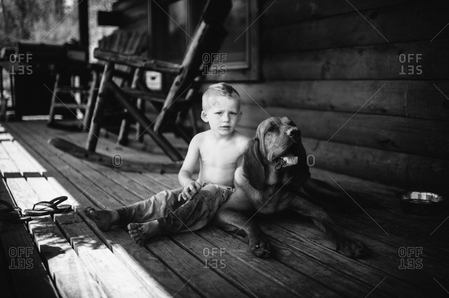 A boy sits on his porch with a hound