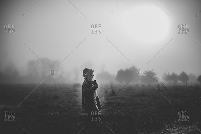 A girl stands in a damp field