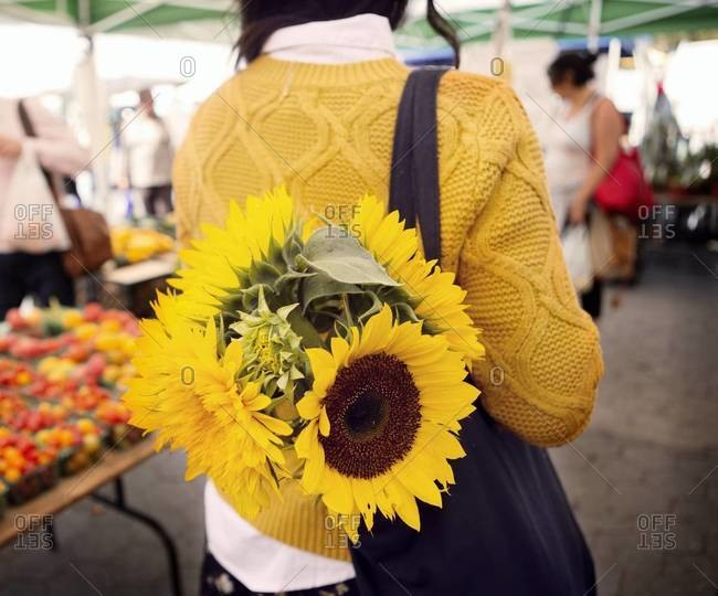 Woman with sunflowers in tote bag