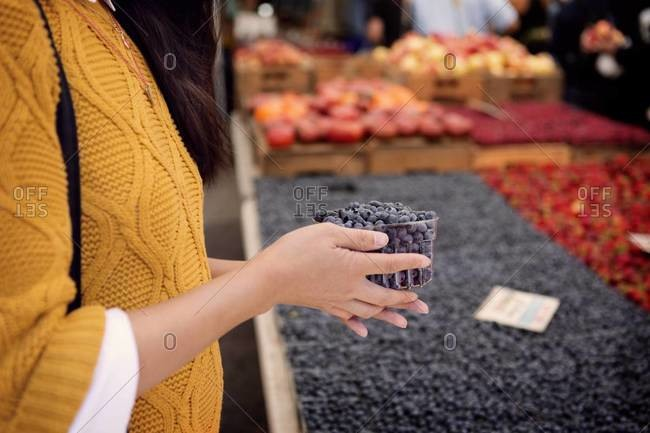 Woman in market buying blueberries