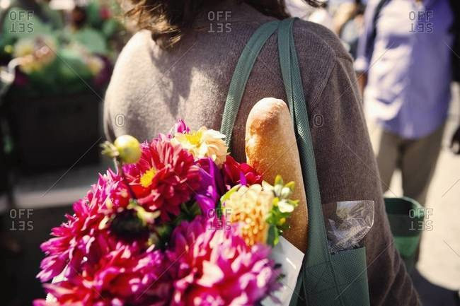 Woman with flowers and bread in tote bag