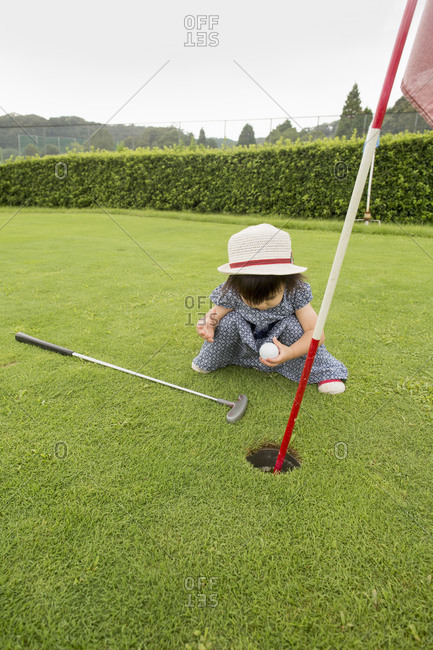 Young girl sitting by a golf course hole