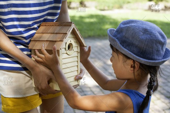 Young girl examining a bird house