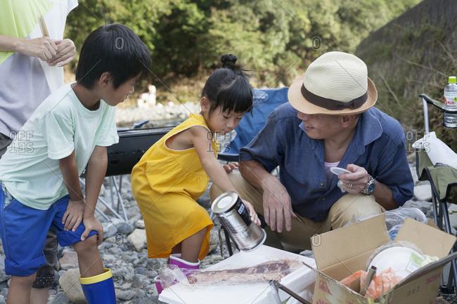 Family preparing food for riverside picnic
