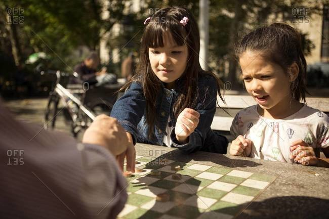 Man and two girls playing checkers in park