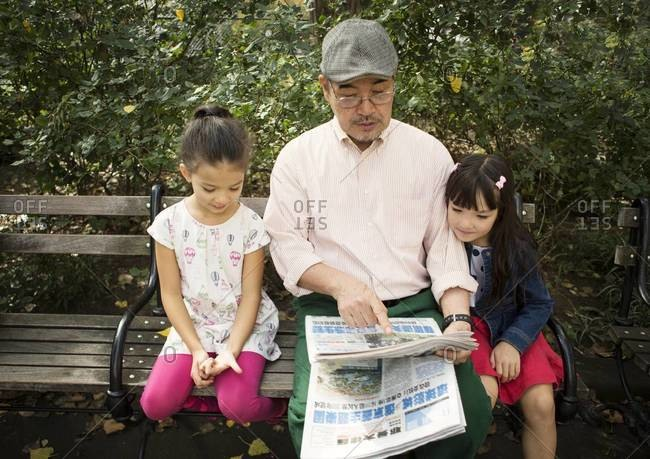 Man and two girls reading Asian newspaper in park