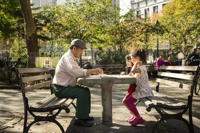 Man and two girls at checkers table in park