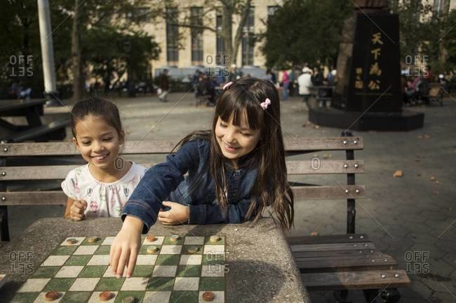 Girl moving checkers piece in park