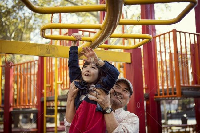 Girl on monkey bars being helped by man