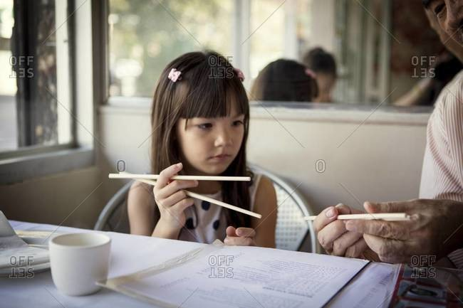 Man showing girl how to use chopsticks