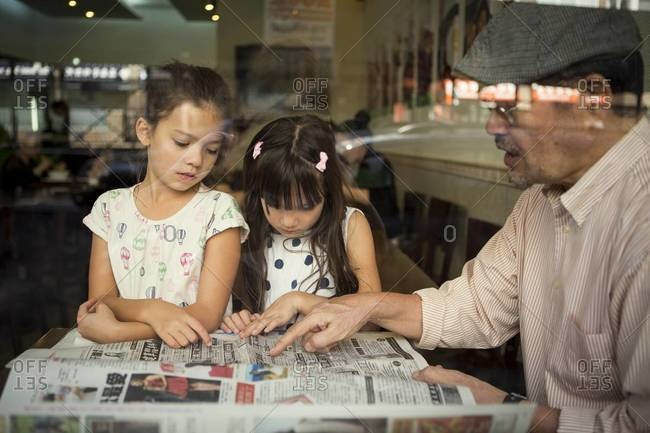 Man and girls reading newspaper in restaurant