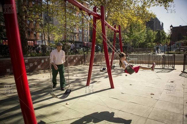 Man pushing girl on swing in playground