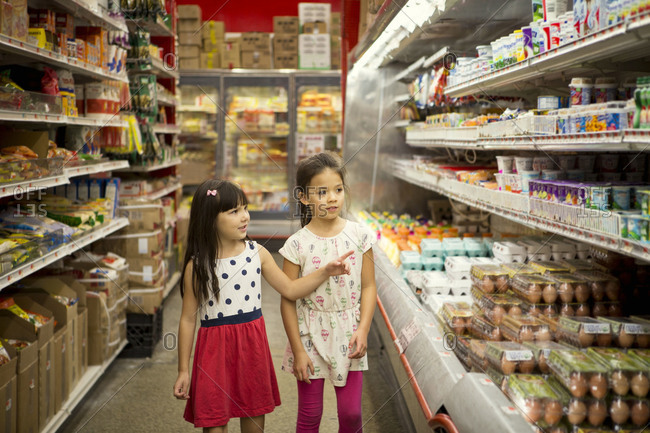 Two girls in dairy aisle in store