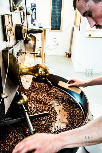 Close up of a man roasting coffee beans with a roaster machine