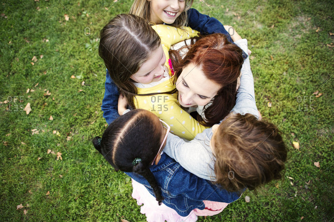 Young girls hugging their chaperone in a park