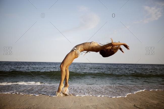 Woman doing backflip on beach