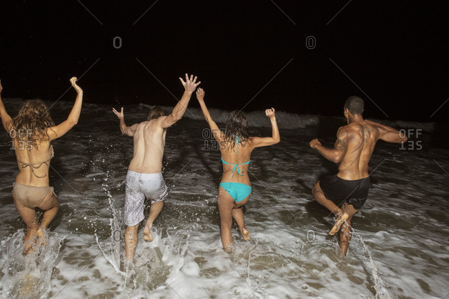 Friends running into the water on the beach at night