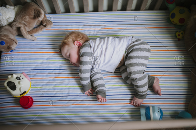 A baby naps in his crib