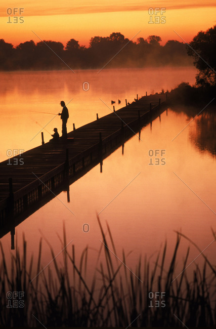 A man fishes along a dock