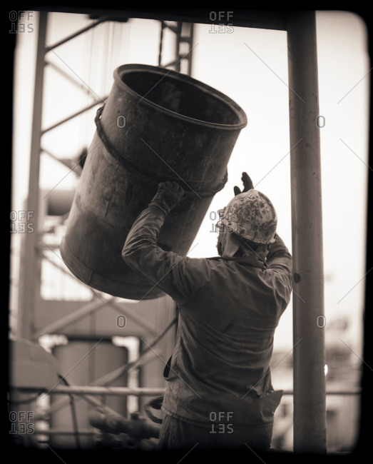 Oilfield worker guides a large barrel on the rig