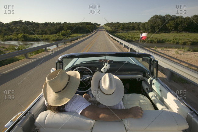 A couple takes a drive in their open top white car down Texas highways wearing cowboy hats