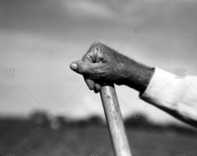 Detail of an older African American man's hand holding on to the tip of a shovel
