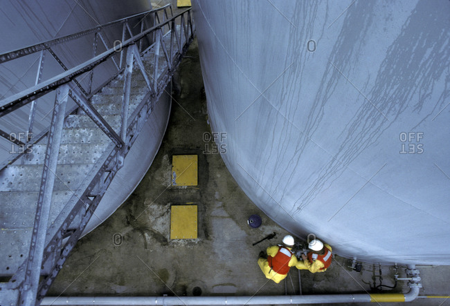 Two men working at the bottom of cylinder shaped silos