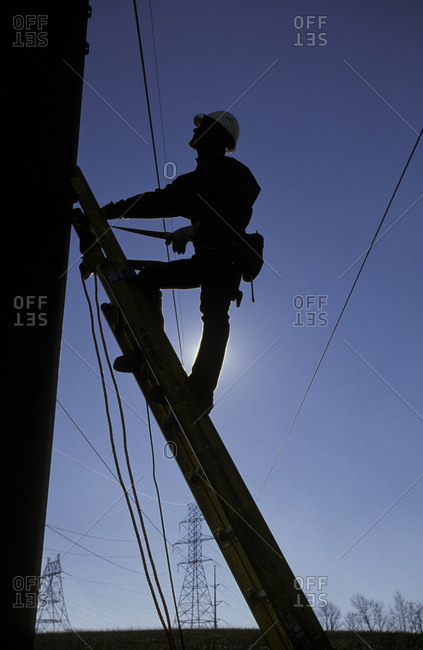 Silhouette of an electrician climbing up an electrical pole for check-up and repair