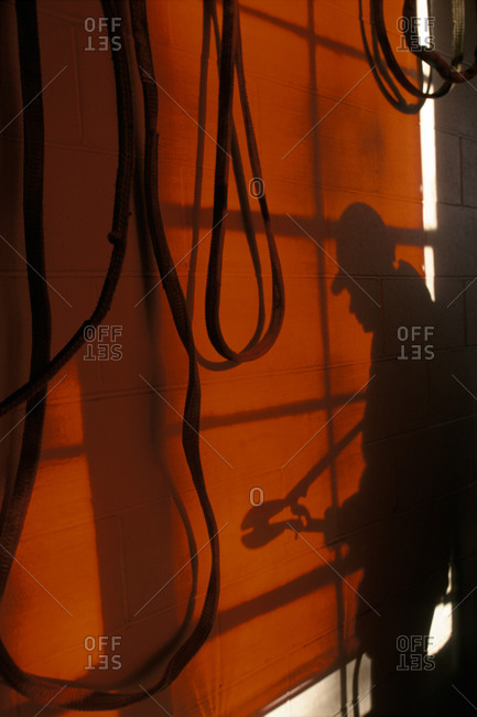 Silhouette over a red wall with wires hanging down of a man with a wrench