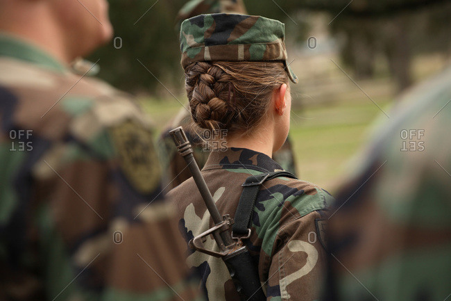 A young caucasian female cadet stands firm during a class call